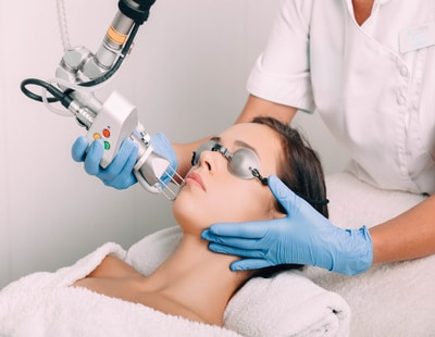 woman wearing protective glasses, getting laser facial treatment. Facial skin rejuvenation