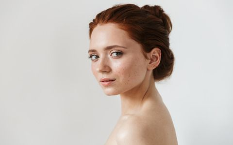 Portrait of a pretty young redhead woman posing isolated over white wall background.