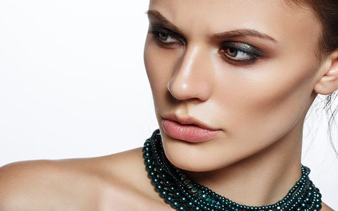 Elegant young lady with evening smart make up and beautiful necklace jewelry on her neck. Gorgeous woman face.
