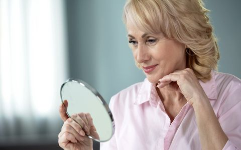 Lady over 50 looking at herself in mirror, rejoicing at result of skin lifting