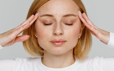 Woman meditating and massaging her temples, closes eyes, relieves emotional stress and nervous tension, exhausted from overwork, isolated on grey background. Fatigued worker suffering from headache.