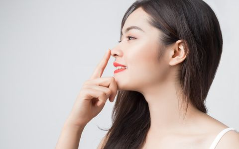 Young beautiful Asian woman with smiley face and red lips touching her nose.