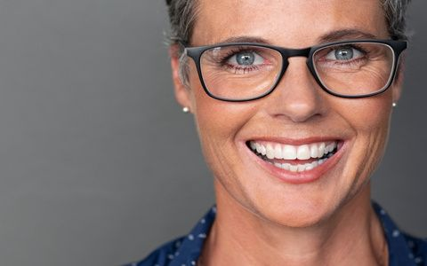 Portrait of happy mature woman wearing eyeglasses and looking at camera. Closeup face of smiling senior woman against grey wall wearing spectacles. Successful businesswoman feeling happy wearing glasses on gray background with copy space.