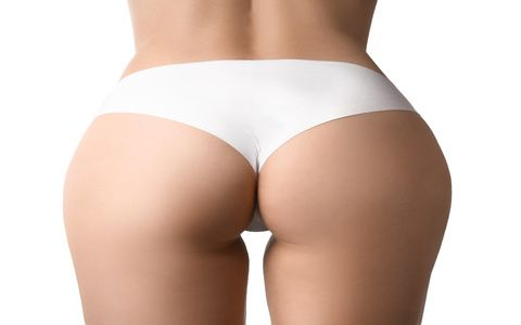 Buttocks of beautiful young woman on white background