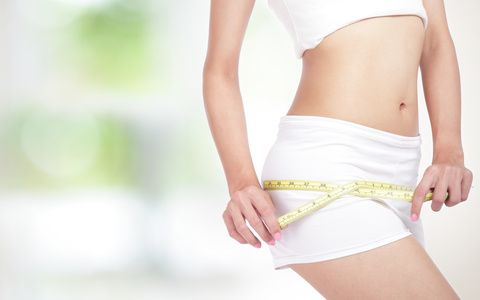 close up of Young Woman measuring perfect shape of beautiful hips. Healthy lifestyles concept, with green background